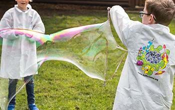 2 boys in mad science lab coats playing with a bubble